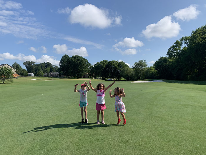 three kids jumping on the golf course